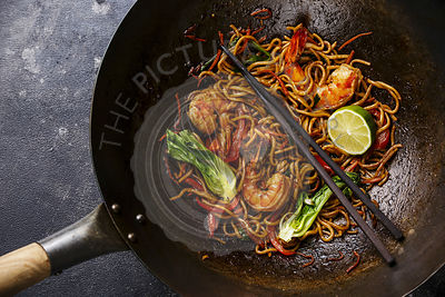 Udon noodles stir-fried with Tiger shrimps and vegetable in wok cooking pan close-up