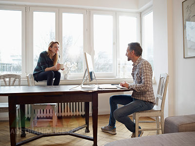 Germany, Cologne, Mature man and adult daughter at home, working at computer