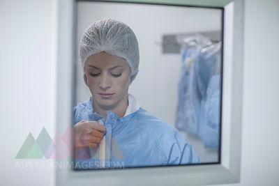 Woman behind glass pane putting on sterile protective clothing