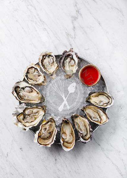 Open Oysters with spicy sauce on white marble background copy space