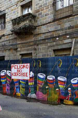 Mural with chunchus dancers painted on corrugated iron fence around building site, Tarija, Bolivia