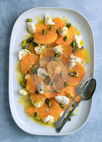 Sliced orange; bocconcini pieces and pistachio nuts covered with a spicy dressing.