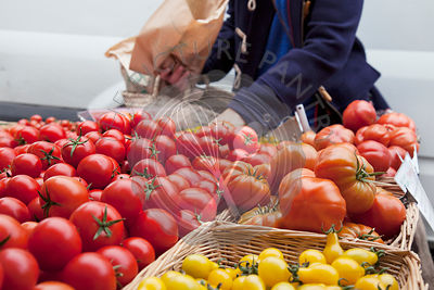 Person choosing tomatoes from baskets on market stall