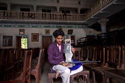 India - Chandannagar - Umesh Mishra, 26 a sarangi virtuoso tunes his instrument before a concert later that night at the Nrit...