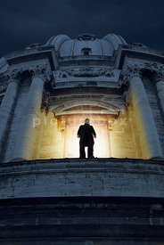 An atmospheric image of a mystery men on a ledge in Rome, Italy.