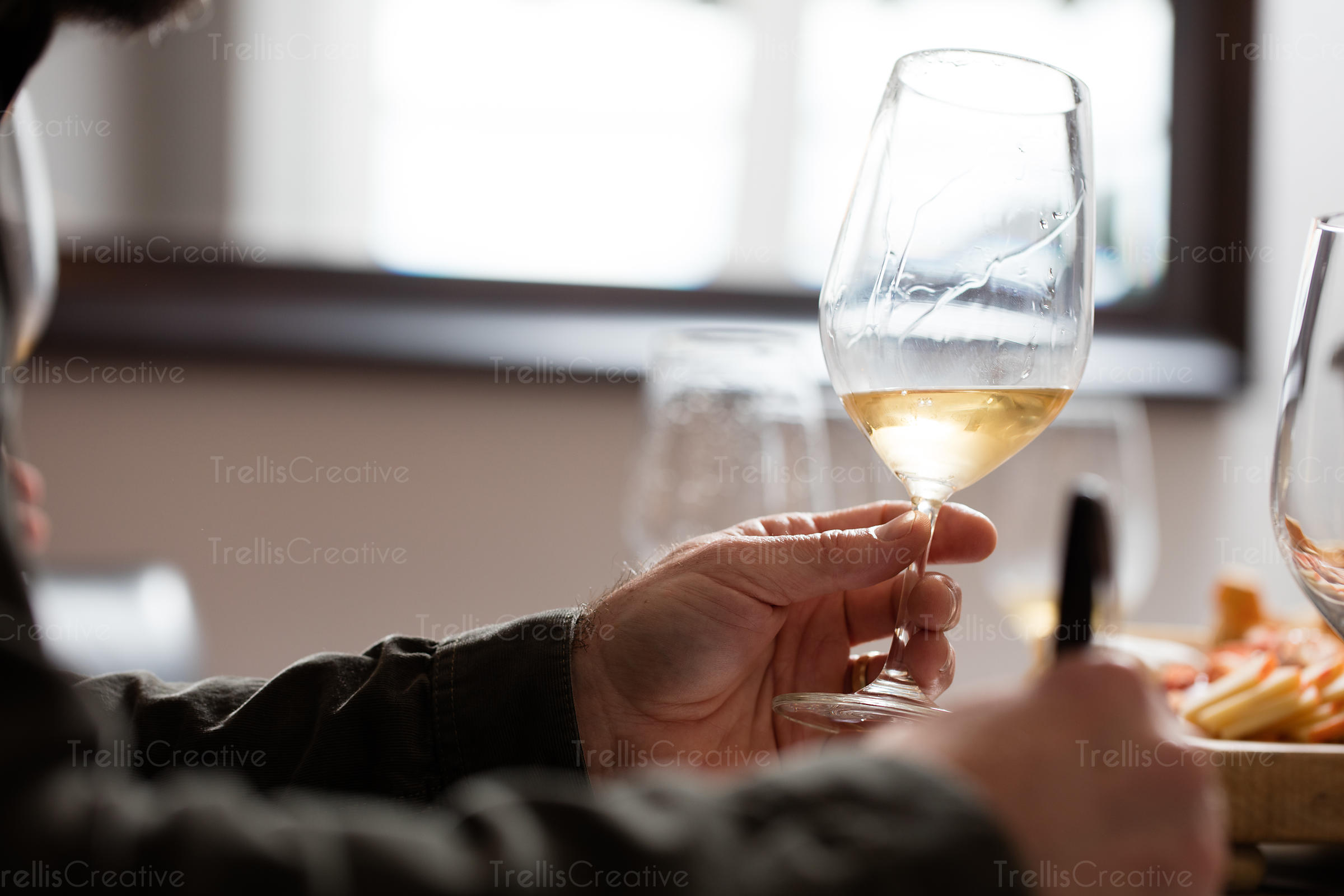 Close-up of a person's hand with wine glass taking notes