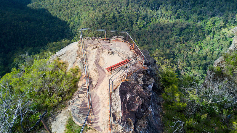Overhead views to a small rocky outcrop and fenced lookout into the valley below.  Blue Mountains Australia