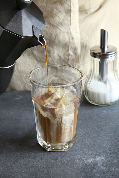 Pouring coffee in a glass over a dollop of ice cream
