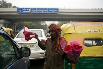 India - Delhi - Govardhan sells flowers to motorists at a busy crossing next to the flyover where he lives with his family
