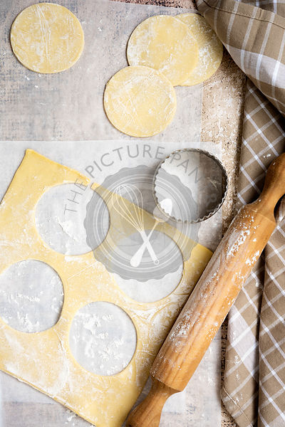 Circles of pastry with a biscuit cutter and rolling pin.