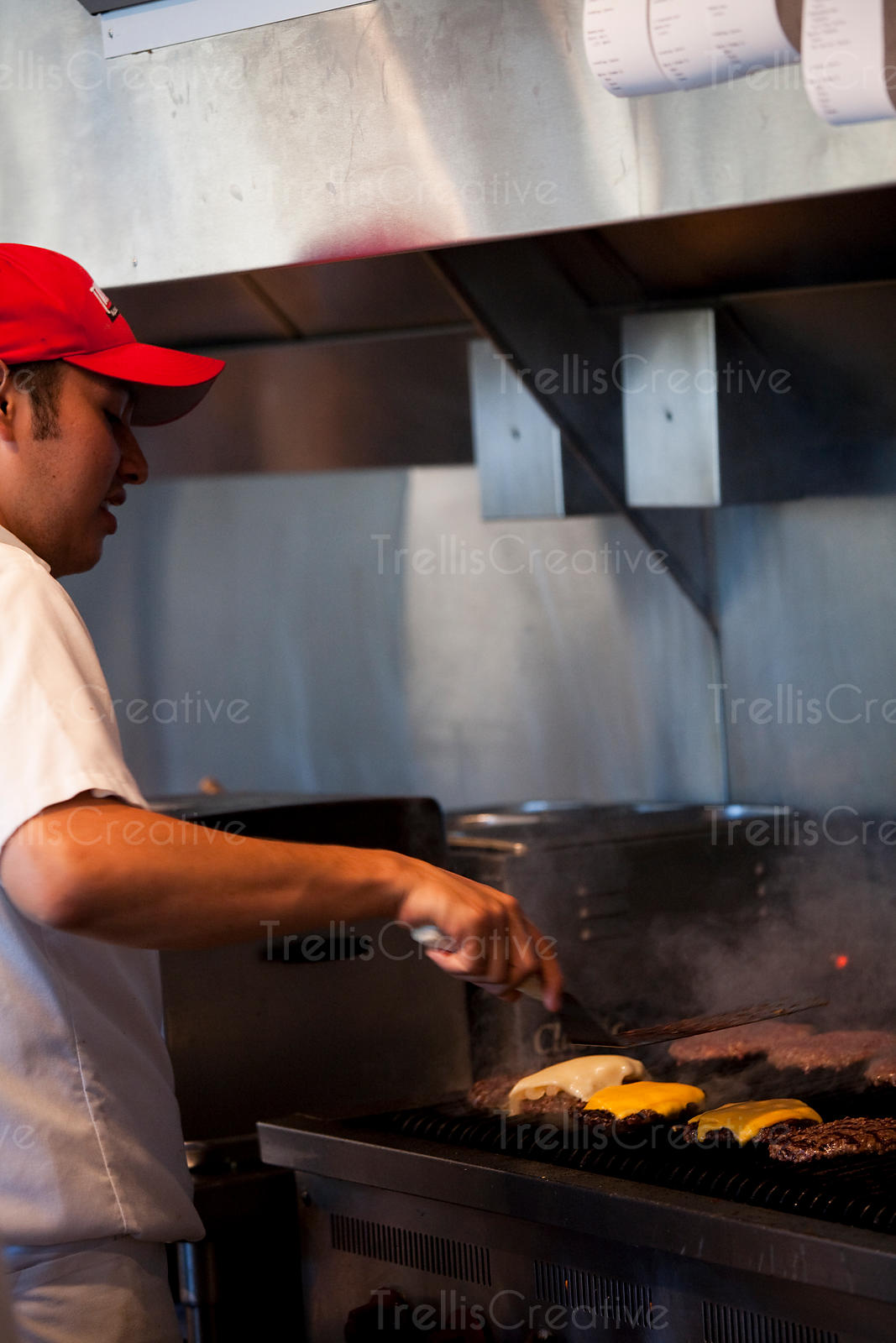 Chef cooking hamburgers over open flame grill