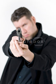 An atmospheric image of a man pointing a gun.