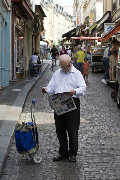 France - Paris - An elderly man reads his  newspaper on the street on the Rue Mouffetard.