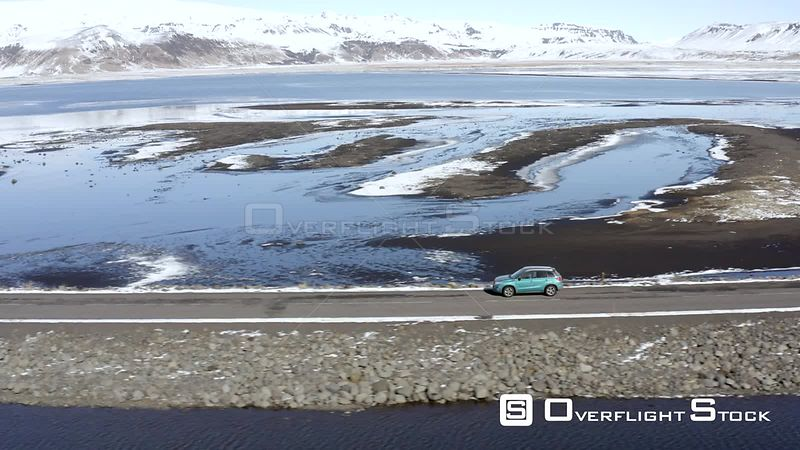 Car Driving Along a Narrow Road Over a Lake in Winter Conditions