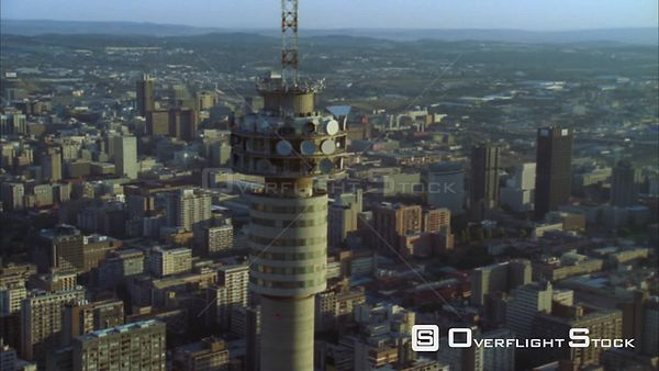 Aerial of the Hillbrow Tower moving further away to reveal Johannesburg Central Business District during early morning/evenin...