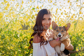 Young Hispanic Woman and Pembroke Welsh Corgi smile in a mustard field