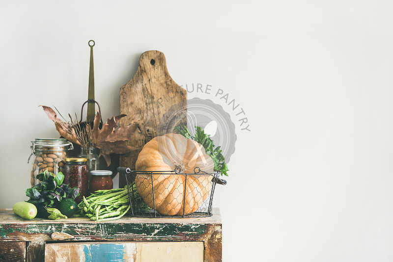 Vegetables, pumpkin, canned food, fallen leaves over rustic wooden chest of cupboard