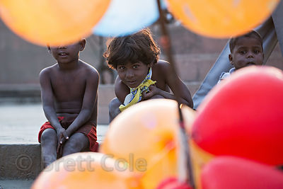 Children peer through balloons during the Kali Murti festival, Assi Ghat, Varanasi, India