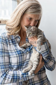 A mature woman planting a kiss on a grey tabby kitten's head
