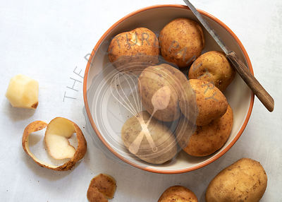 Brushed potatoes in a bowl with one peeled potato.