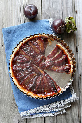 Freshly baked  plum tart on wooden board
