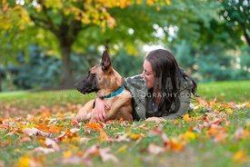 belgian malinois looking away from mom in grass and autumn leaves