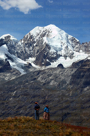 Local couple on hilltop near La Cumbre in front of Mt Illampu, Cordillera Real, Bolivia