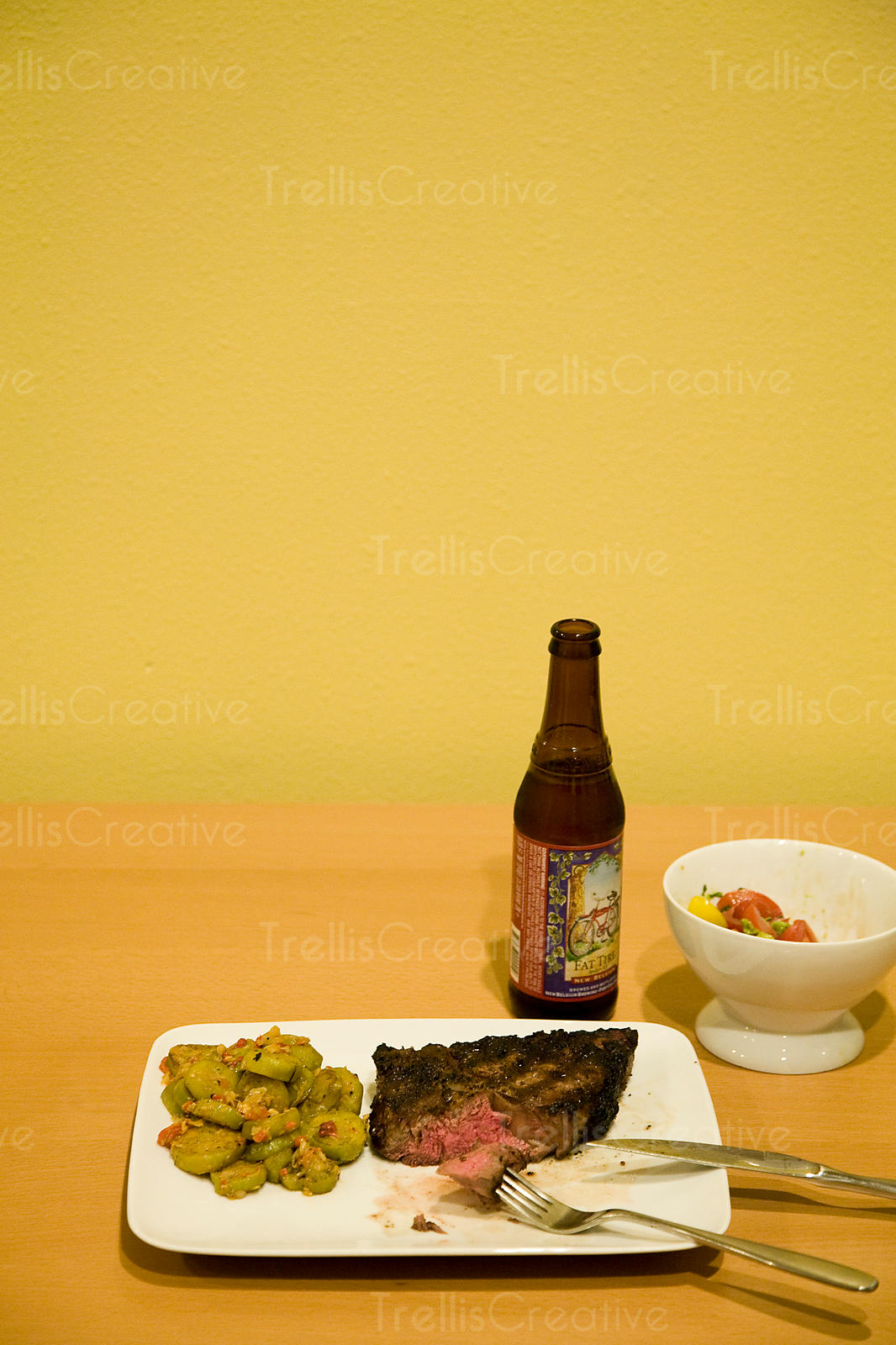 A rare steak with side dishes and a beer