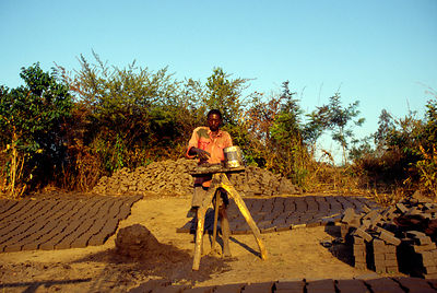 Burundi - Ruyigi - A man making bricks from mud in a field