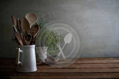 Rustic still life of a kitchen counter with worn wooden utensils in a porcelain pitcher and a lovely tangled oregano plant in...
