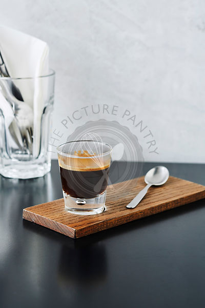 Close-up of a shot of espresso on wood board