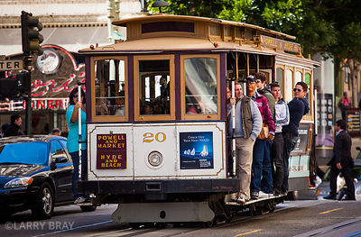Cable car with passengers standing on footplate at side in San Francisco, USA