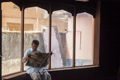 India - Kannur - A man sits reading the morning newspaper in the Indian Coffee House at the Plaza Building