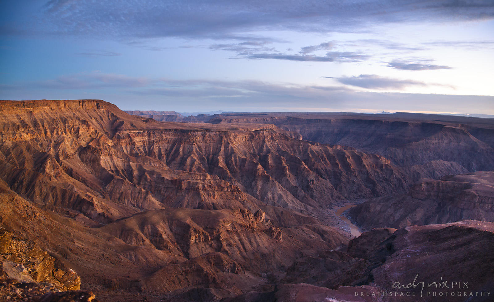 View of a large, deep, desert canyon with a muddy brown river at the bottom at dusk