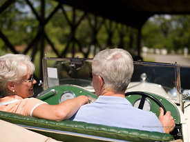 Senior couple riding in a classic car through a covered bridge