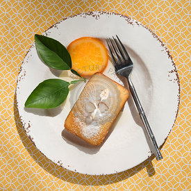 Small orange loaf cake, slice of orange and a fork on a plate.