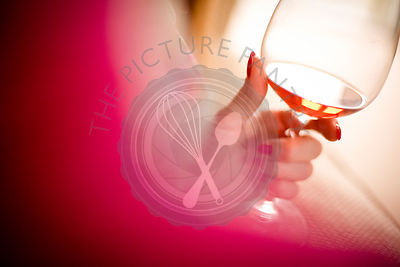 Woman holding a glass of rose wine. Sun is reflected off the glass and wine.