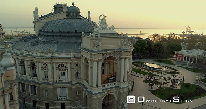 Aerial camera tracks slowly sideways pass  the Odessa Opera Theatre. The sun is rising over Black Sea behind Ukraine