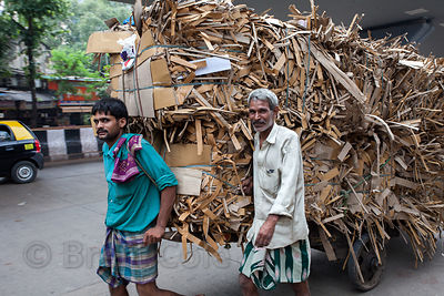 Men pull a cart with shredded cardboard for recycling, Lalbaug, Mumbai, India.