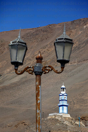 Rusting street lamp and old clock tower on hillside above Pisagua , Region I , Chile