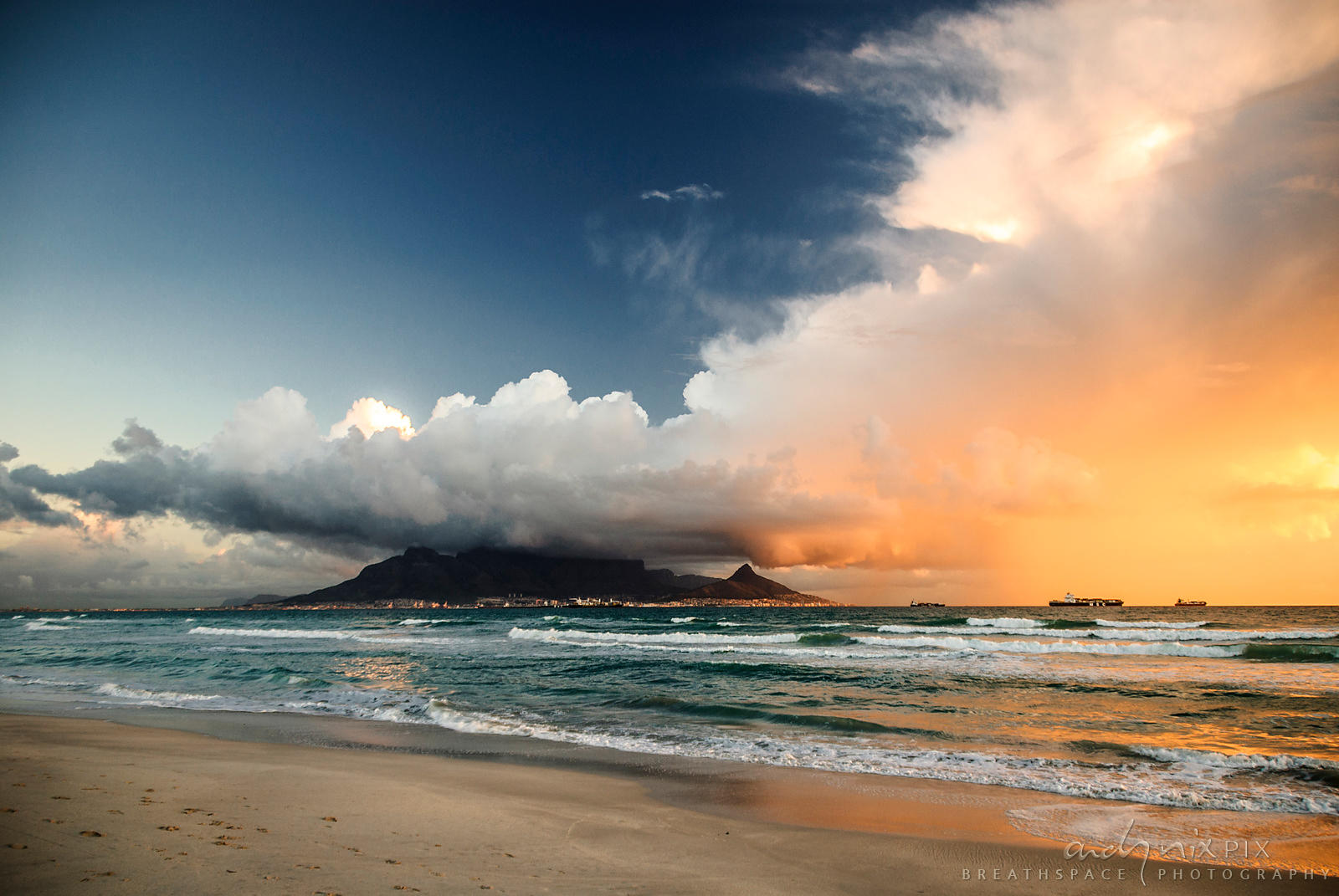 Last rays of sun light up storm clouds gathering over Table Mountain.