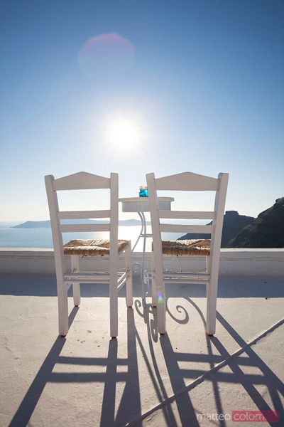 Two empty chairs overlooking blue mediterranean sea Santorini Greece