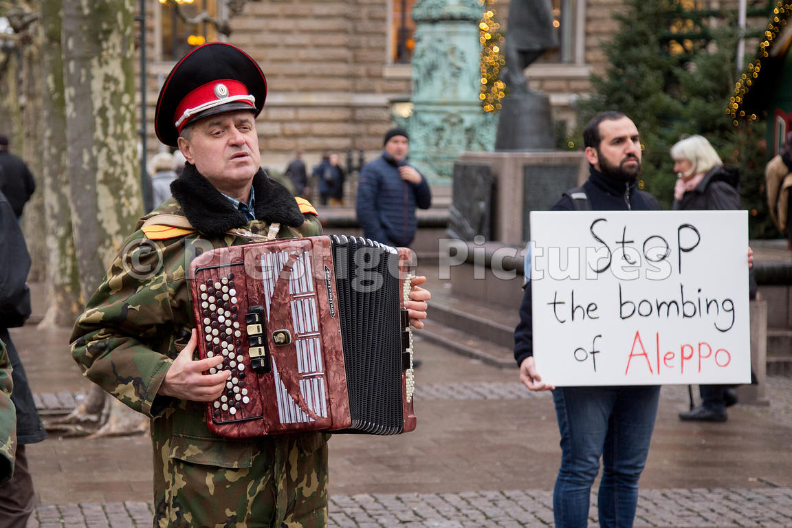 Alleppo Bombing Protestor and the Cossack Choir accordianist at the Hamburg Rathausmarkt Christmas Market