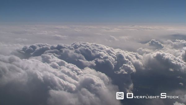Flying alongside lumpy cloud mass, passenger POV