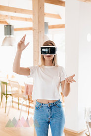 Young woman wearing VR goggles, designing her new home