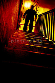 An atmospheric image of a silhouetted mystery man standing at the top of some steps, holding a gun.