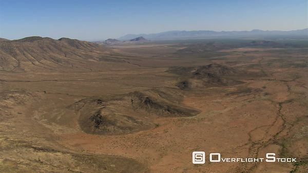 Slow flight past barren desert landscape with low mountains in background