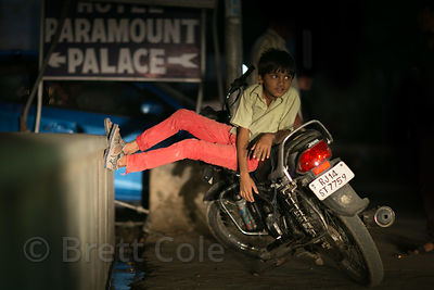 A boy hangs out on a motorcycle at night, Pushkar, Rajasthan, India