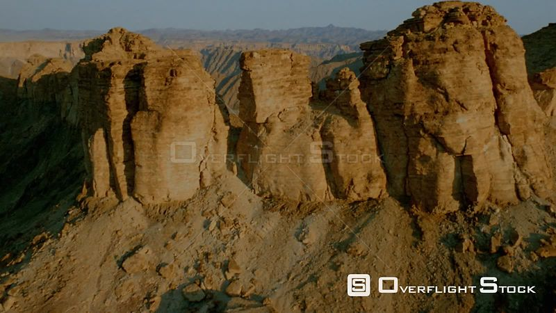 Aerial shot sun shinning on side of mountain and cliff face, over the top and down side of mountain in shadow to wide shot of...