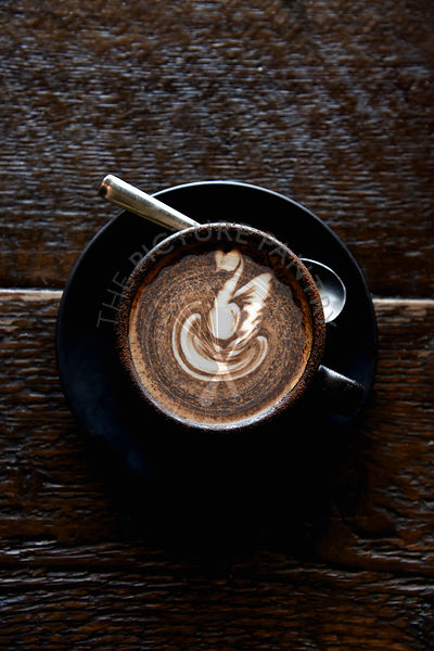 A coffee in a black cup and saucer, with a white milk swirl on a wooden background.